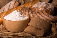 Whole wheat bread,flour and cloth bag on wood table. stock photography