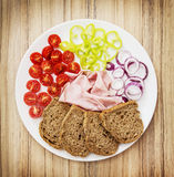 Whole wheat bread with ham, onion, paprika and cherry tomatoes Royalty Free Stock Photo