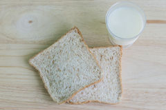 Whole Wheat bread and milk. On the table wooden Royalty Free Stock Photos