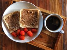 Whole wheat bread with peanut butter and tomatoes in white dish with Black coffee cup royalty free stock images