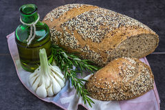 Whole wheat bread and rye, sprinkled with sunflower seeds, poppy seeds, sesame seeds, next to a bottle of olive oil, rosemary and Royalty Free Stock Photography
