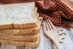 Whole wheat bread and spike on white wooden table Royalty Free Stock Images