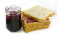 Whole wheat bread stack with grape jam on isolated white background. Royalty Free Stock Images