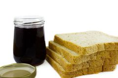 Whole wheat bread stack with grape jam on isolated white background. Stock Image