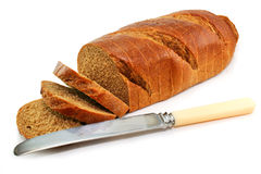 Whole wheat bread and table knife isolated. On a white background Stock Photo