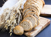 Whole wheat bread with wheat ears and seeds , bread slices on wo. Oden board Stock Photo