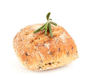 Whole wheat bun with seeds and a sprig of rosemary. Stock Images