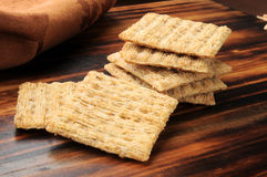 Whole wheat crackers. Closeup of whole wheat crackers on a chopping block Stock Photos