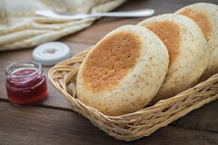 Whole wheat english muffins in basket and strawberry jam in bott Stock Images
