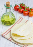 Whole wheat flour tortillas with tomatoes and olive oil. On the background Royalty Free Stock Photo