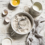 Whole-wheat flour in white bowl, milk, eggs on a light wooden background. Royalty Free Stock Images