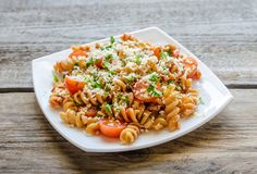 Whole wheat fusilli pasta with cheese and cherry tomatoes Stock Photos