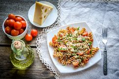 Whole wheat fusilli pasta with cheese and cherry tomatoes Stock Photo
