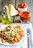 Whole wheat fusilli pasta with cheese and cherry tomatoes. Whole wheat fusilli pasta with cherry tomatoes stock image
