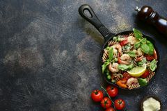 Whole wheat fusilli pasta with shrimps and vegetables in a skill. Et on a dark slate, stone, concrete or metal background.Top view with copy space stock photography