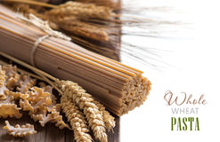 Whole wheat italian pasta with wheat spikes Royalty Free Stock Photos