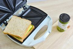 Whole wheat  matcha and cheese sandwich on a toaster. Ready to cook Royalty Free Stock Photography