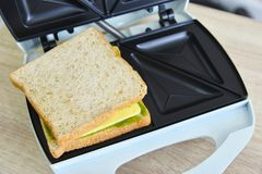 Whole wheat  matcha and cheese sandwich on a toaster. Ready to cook Royalty Free Stock Photo