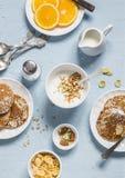 Whole wheat pancakes, greek yogurt with homemade granola, orange slices, nuts, corn flakes, on a blue stone background. Royalty Free Stock Photos