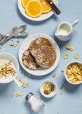 Whole wheat pancakes, greek yogurt with homemade granola, orange slices, nuts, corn flakes, on a blue stone background. Royalty Free Stock Photo