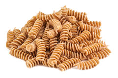 Whole wheat pasta. Heap of whole wheat pasta on white background Stock Photos