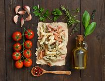 Whole wheat pasta, olive oil, vegetables and herbs. On a wooden background Stock Photography