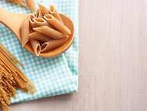 Whole wheat pasta option. Whole wheat pasta - spaghetti and short pasta penne in wooden spoon on checkered table cloth on wooden table, copy space Stock Image