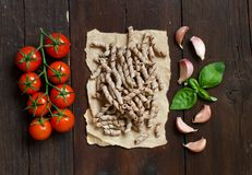 Whole wheat pasta, tomatoes, basil and garlic. On a wooden background Stock Photo