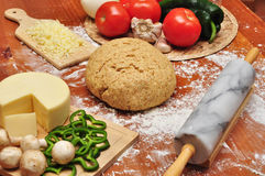 Whole Wheat Pizza Dough. Pizza ingredients and whole-wheat dough on a wooden table sprinkled with flour Stock Photo