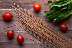 Whole wheat spaghetti with ramson and tomatoes on wood table Royalty Free Stock Image
