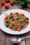 Whole wheat spaghetti with ramsons, tomatoes and olives on wood table Stock Photo