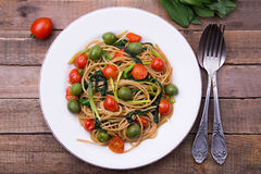 Whole wheat spaghetti with ramsons, tomatoes and olives on wood table. Whole wheat organic spaghetti with wild leek, tomatoes and green olives on wood table with Royalty Free Stock Photo