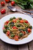 Whole wheat spaghetti with ramsons, tomatoes and olives on wood table Stock Photography