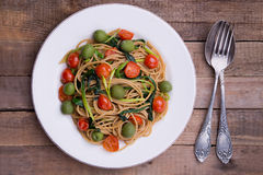 Whole wheat spaghetti with ramsons, tomatoes and olives on wood table Stock Photos