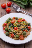 Whole wheat spaghetti with ramsons, tomatoes and olives on wood table. Whole wheat organic spaghetti with wild leek, tomatoes and green olives on wood table with Stock Images