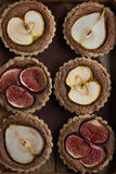 Whole wheat tarts  with chocolate frangipane, figs, apple and pe Stock Photos