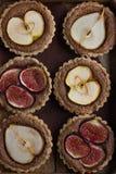 Whole wheat tarts  with chocolate frangipane, figs, apple and pe Stock Photos