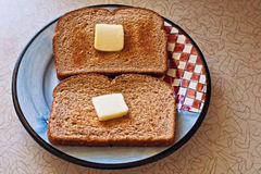 Whole wheat toast. Two slices of fresh toast on a plate with pats of butter on old fashioned counter Royalty Free Stock Image