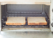 Whole wheat toast in the oven. Royalty Free Stock Photography