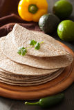 Whole wheat tortillas on wooden board and vegetables Stock Images