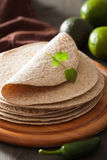 Whole wheat tortillas on wooden board and vegetables Royalty Free Stock Image