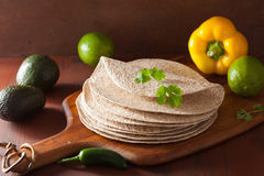 Whole wheat tortillas on wooden board and vegetables Royalty Free Stock Photos
