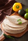 Whole wheat tortillas on wooden board and vegetables Royalty Free Stock Photography