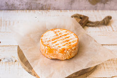 Whole wheel of soft French, German cheese with orange rind with mold on parchment paper, wood cutting board, concrete wall Stock Photos