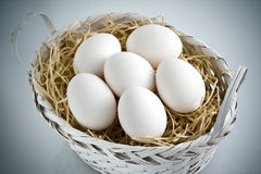 Whole White Eggs on Straw White Basket royalty free stock images