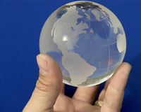 The whole world on blue. A hand holding a glass globe Stock Image