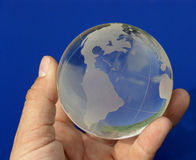 The whole world on blue 2. A hand holding a glass globe Royalty Free Stock Photography