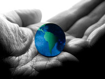 Whole world in his hands. A macro of the world in a hand Royalty Free Stock Photography