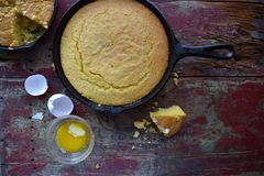 Whole Yellow Cornbread in cast iron skillet with egg shells on rustic wood table closeup top view with copy space. Cast iron skillet of whole yellow corn bread stock image