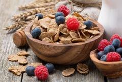 Wholegrain хлопья с ягодами и кувшином молока на деревянном столе Стоковая Фотография